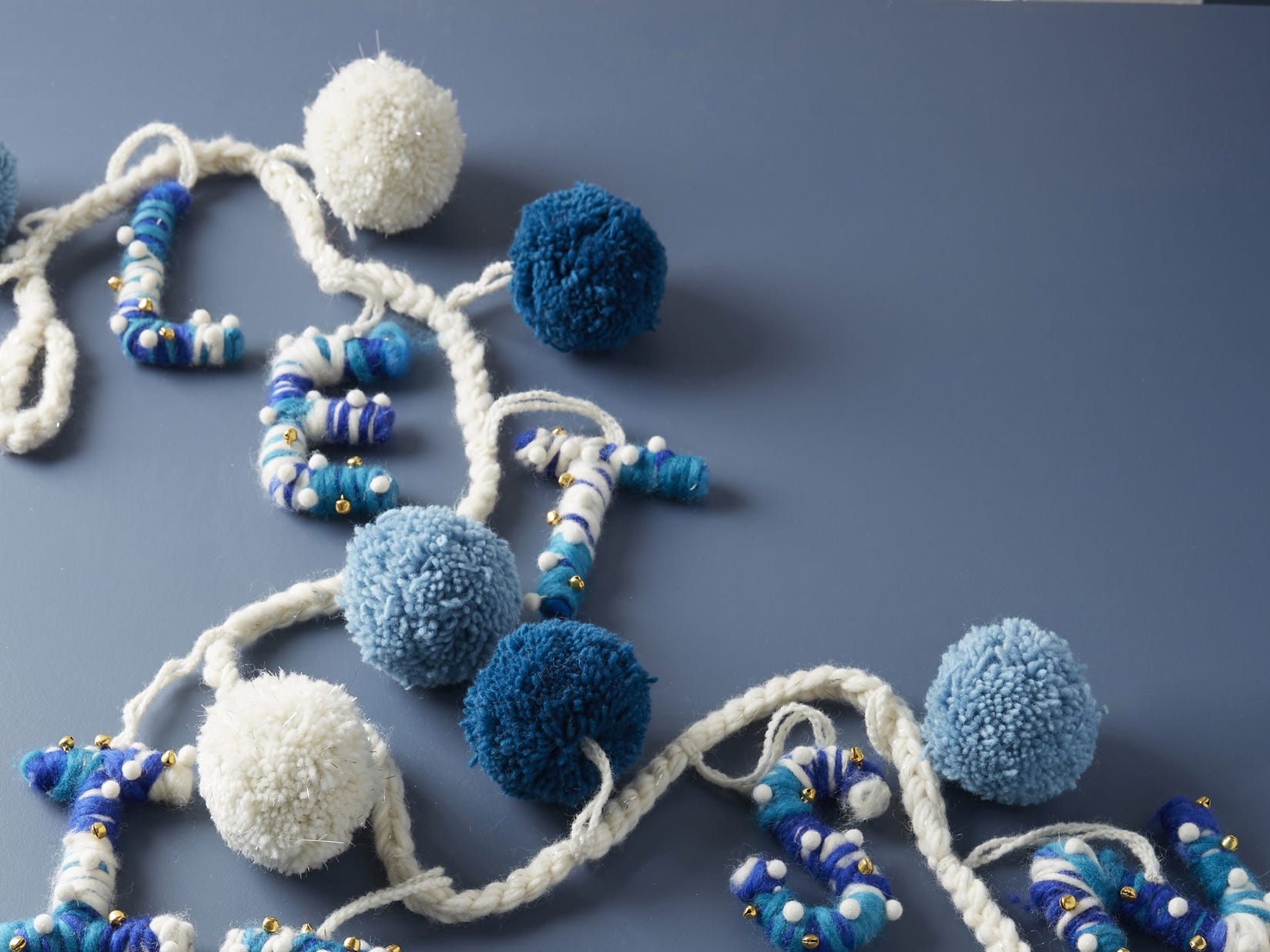 """This homespun touch with blue and white wool yarn and pompoms with subtle gold beads and wrapped letters that spell out """"Let It Snow"""" is a festive option for Hanukkah decorating in a traditional palette."""