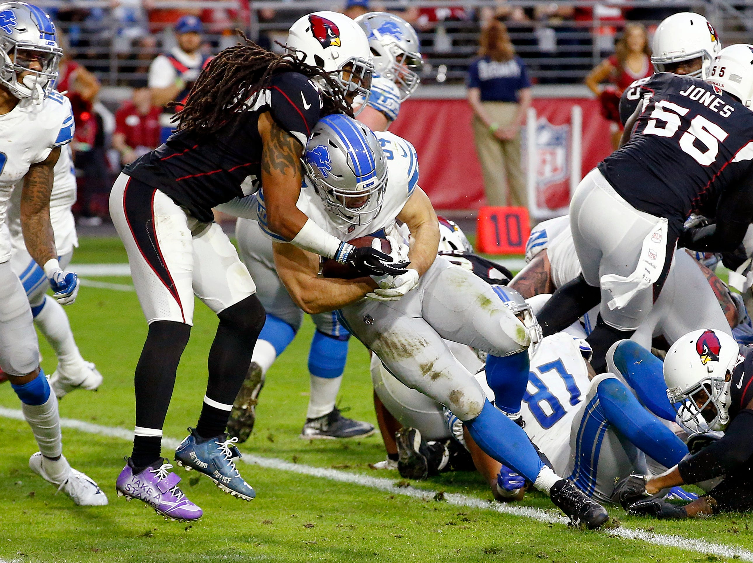 Detroit Lions running back Zach Zenner (34) scores a touchdown as Arizona Cardinals defensive back Tre Boston defends during the second half.