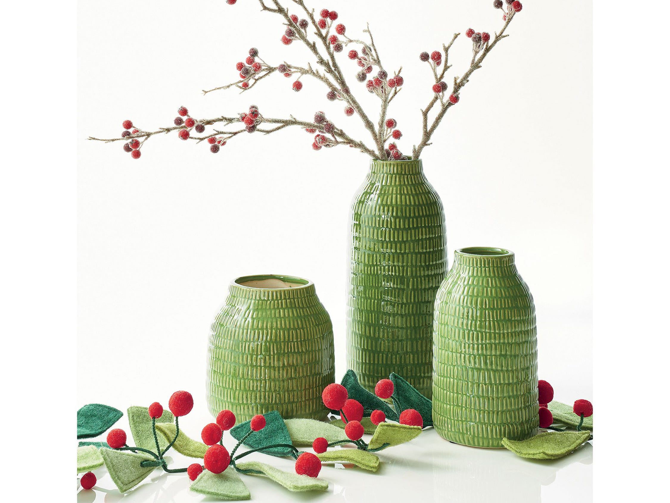 """Simple felt triangle """"needles"""" in two shades of green with clusters of red pompom berries form a handcrafted garland that is part of an attractive tablescape, with textured glazed embossed dash stoneware vases, one holding a berry branch. All are from Crate and Barrel."""