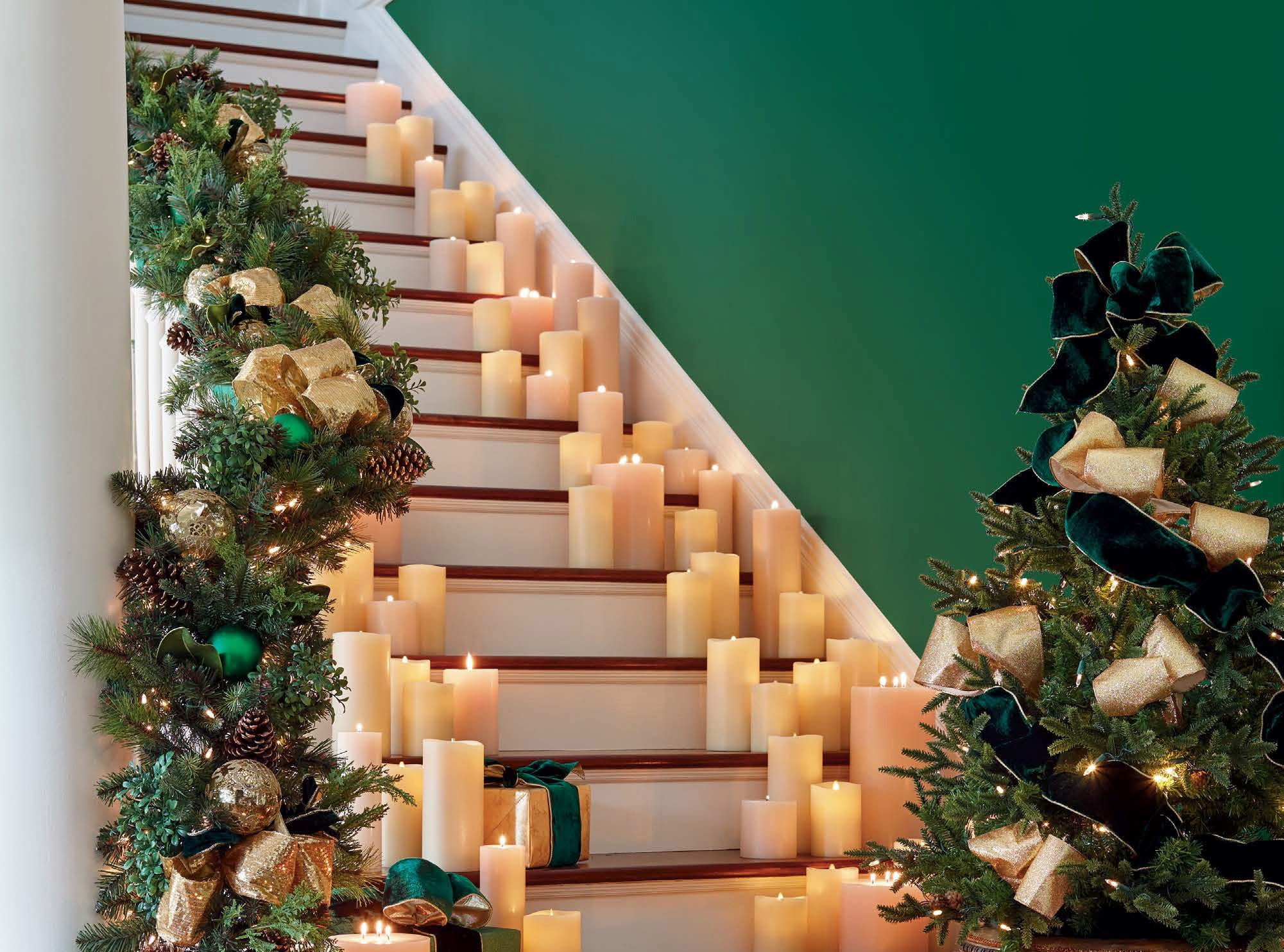 Dozens of flameless candles dreamily line a staircase and a lush garland from Frontgate is draped over the rail. There are large emerald and gold balls, shimmery metallic ribbons, gold-edged forest green velvet ribbons and pine cones that add color, texture and radiance.