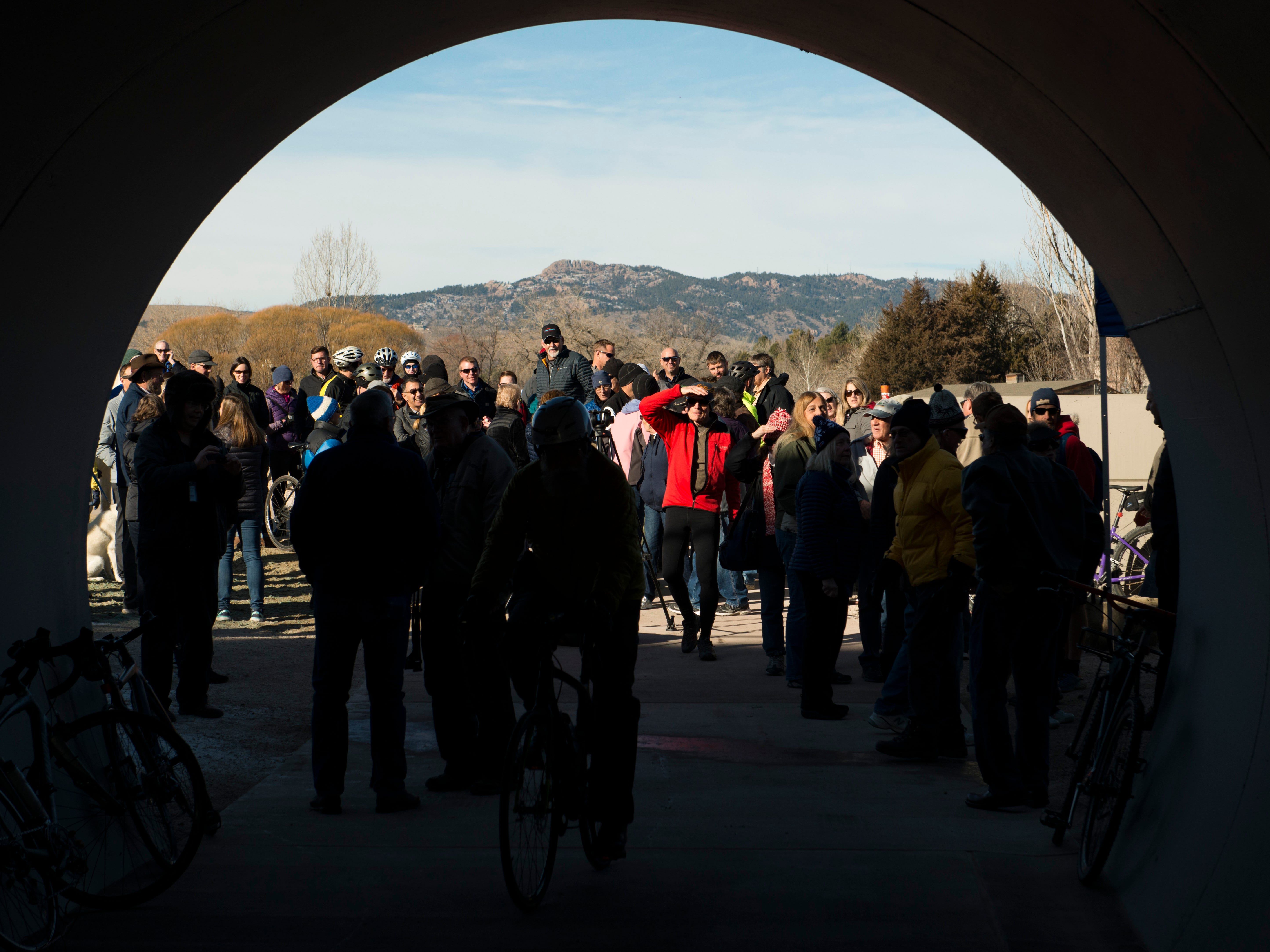 Horsetooth Rock is framed above a crowd through the new 70-foot-long Fossil Creek Trail pedestrian tunnel in south Fort Collins on Monday, December 10, 2018. The new 1.7 mile section of trail runs under the BNSF railway to connect College Avenue and Shields Street.