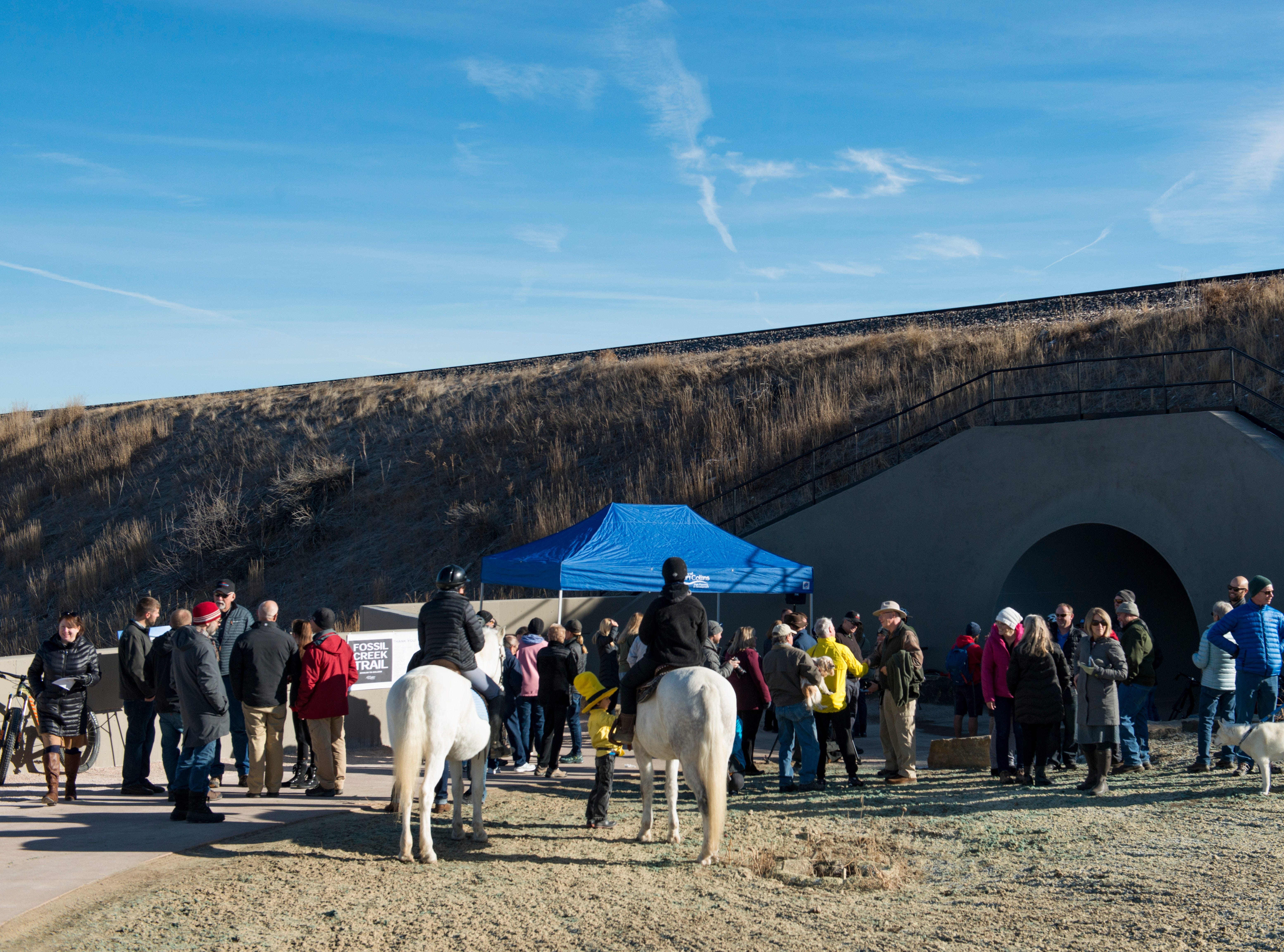 People attend a ribbon-cutting for the new 70-foot-long Fossil Creek Trail pedestrian tunnel in south Fort Collins on Monday, December 10, 2018. The new 1.7 mile section of trail runs under the BNSF railway to connect College Avenue and Shields Street.