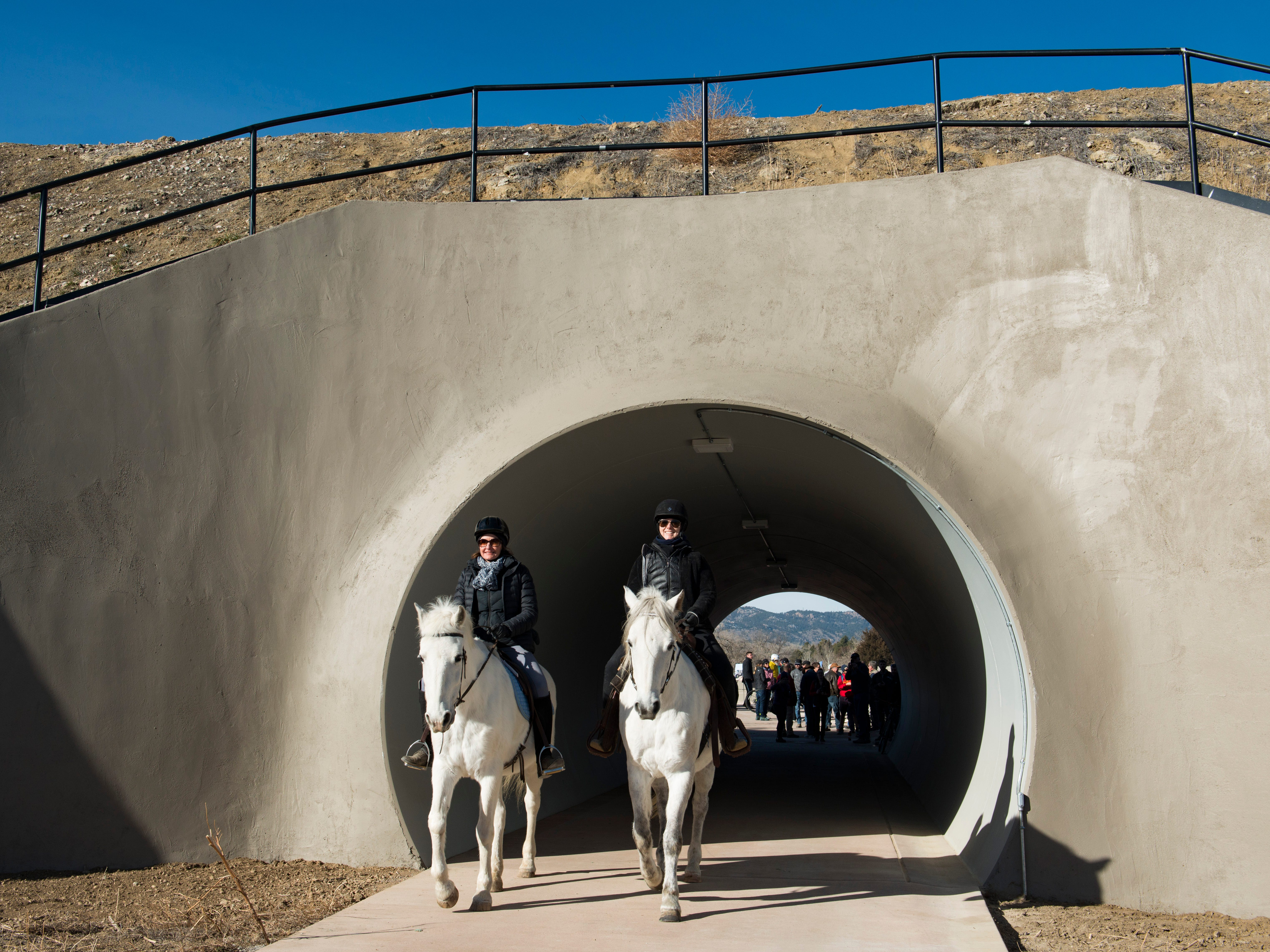 Kate Schoenecker and Sarah King ride their horses, Contare and Brio,  through the new 70-foot-long Fossil Creek Trail pedestrian tunnel in south Fort Collins on Monday, December 10, 2018. The new 1.7 mile section of trail runs under the BNSF railway to connect College Avenue and Shields Street.