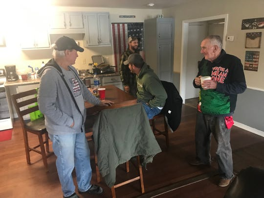 Homeless veterans who are staying at a shelter operated by Fellow Countryman, around the table after breakfast.