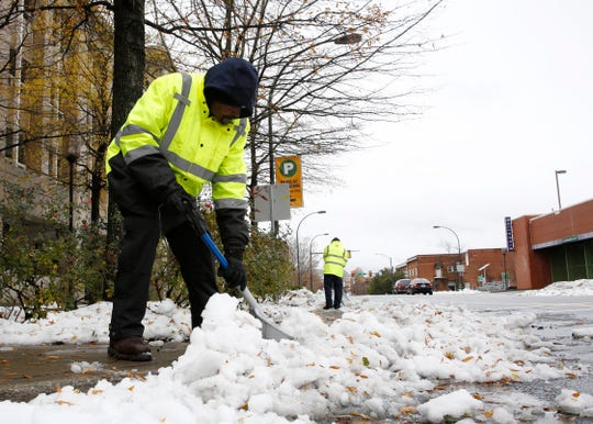 Tony Freeman, with the Public Works Department, shovels snow on McBee Avenue in Greenville Monday, Dec. 10, 2018.