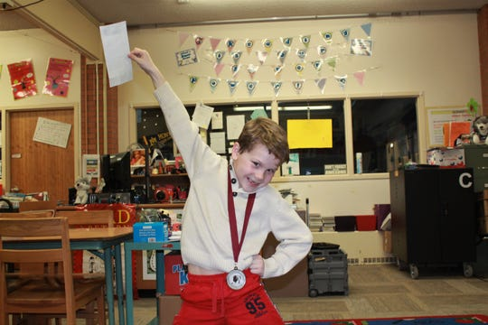 Lincoln Hodson giving his coolest pose with his scholarship and silver medal