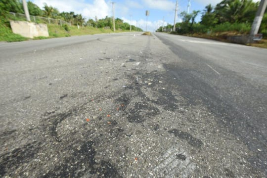 Debris remains on the asphalt at the scene of an early morning motorcycle spill reported at the intersection of Marine Corps Drive and Chalan Lachanch Road in Yigo.