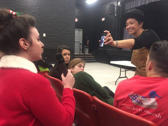 "Henderson native Ane Crabtree, who was nominated for an Emmy twice for her costume design work on ""The Handmaid's Tale,"" holds up her phone so that HCHS student Caris Wilke can ask a question of Joie Lee, a screenwriter and actress."