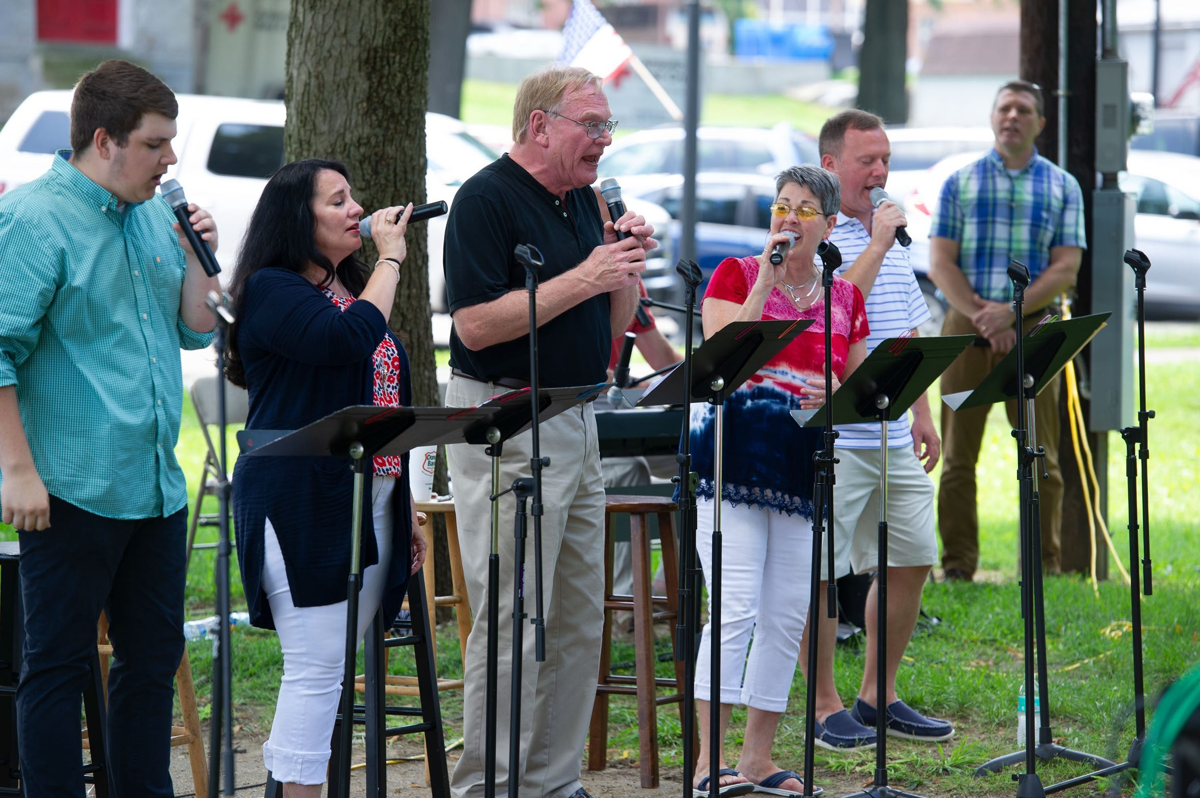 Alan Chamness, center, leads the congregation in signing during First Baptist Church's worship service in Central Park during Memorial Day weekend in May 2018, along with singers (from left), Clay Whitmore, Deanna Meeks, Chamness, Linda Todd-Ferguson and Ben Patterson. Also shown is executive pastor Rich Stratton.