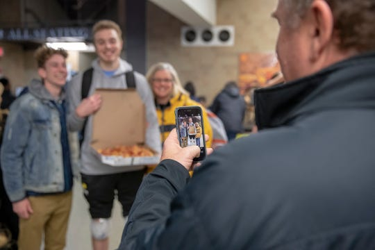 Chuck Hansen photographs his son Jack Hansen and Jack's mother Mary Hansen, as friend Jimmy Huscroft (left), pose after Jack's game against IU Kokomo, Indiana Farmers Coliseum, Indianapolis, Thursday, Dec. 7, 2018. Evan Hansen, a Wabash College senior, and football team captain, took his life in September of 2018.