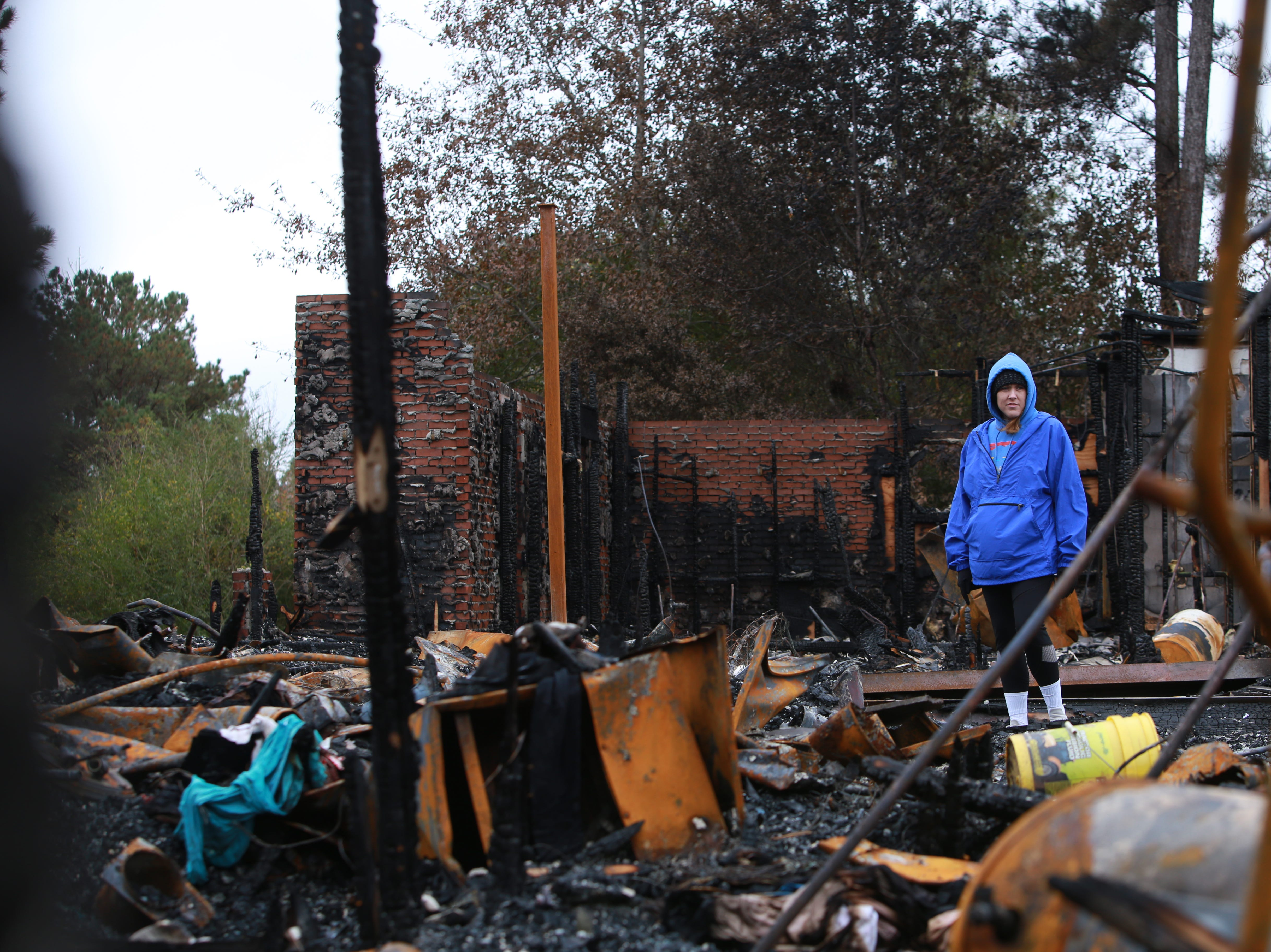 Leigh Haas, 30, stands in the remains of her family'ss 6500 square-foot home in Kiln, Mississippi, that was destroyed by fire on November 25, 2018.