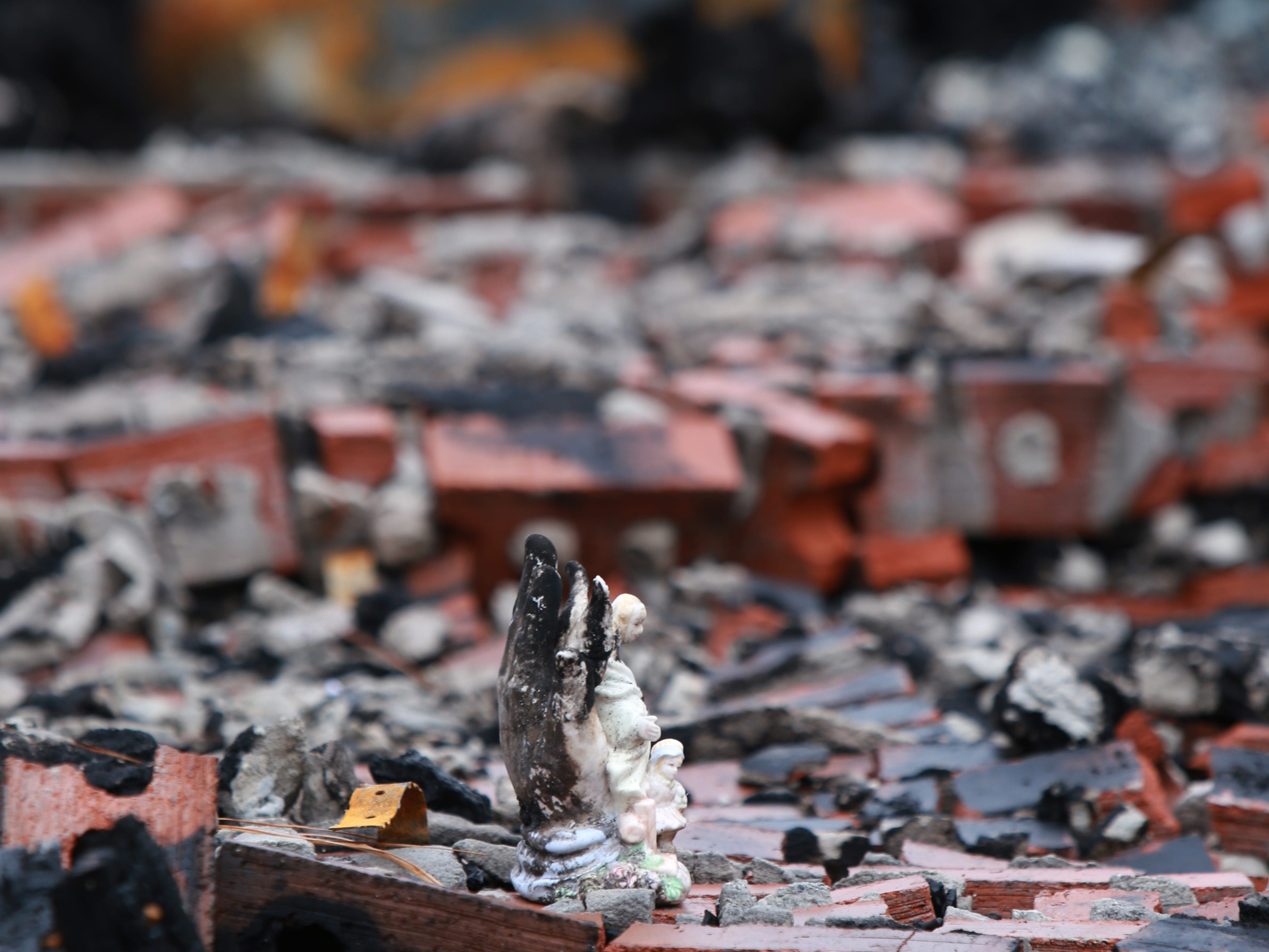 An angel figurine was one of the possessions left in the rubble of a house fire that destroyed the Haas home in Kiln, Mississippi, on Nov. 26, 2018.