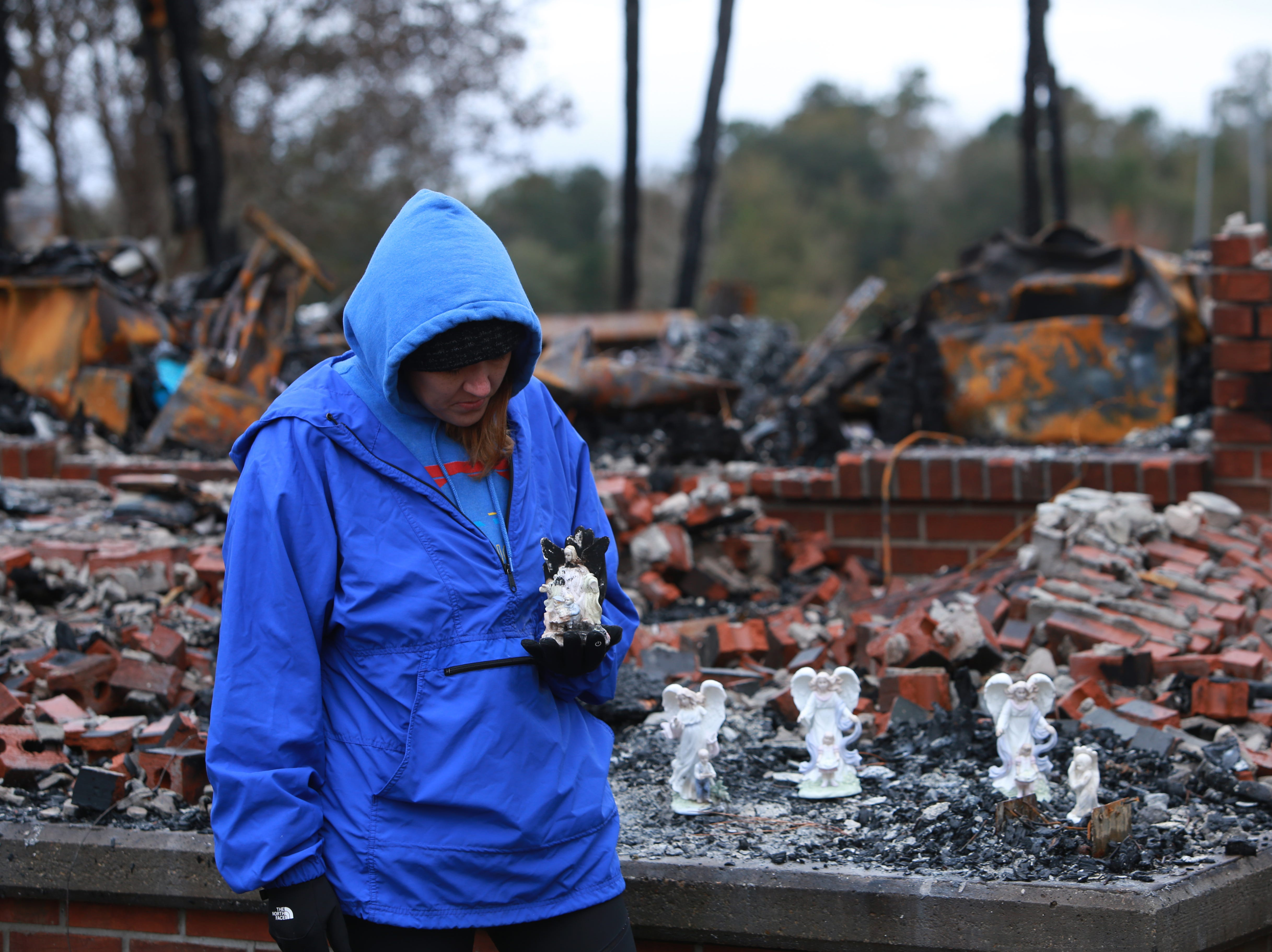 Leigh Haas, 30, holds an angel figurine that was burned but survived a fire that destroyed the Haas family's 6500 square-foot home in Kiln, Mississippi on November 25, 2018.