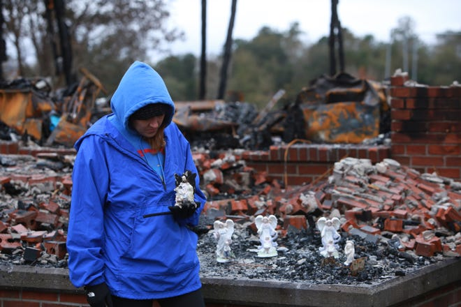 Leigh Haas, 30, holds an angel figurine that was burned but survived a fire that destroyed the Haas family's home in Kiln, Miss., on Nov. 26, 2018.
