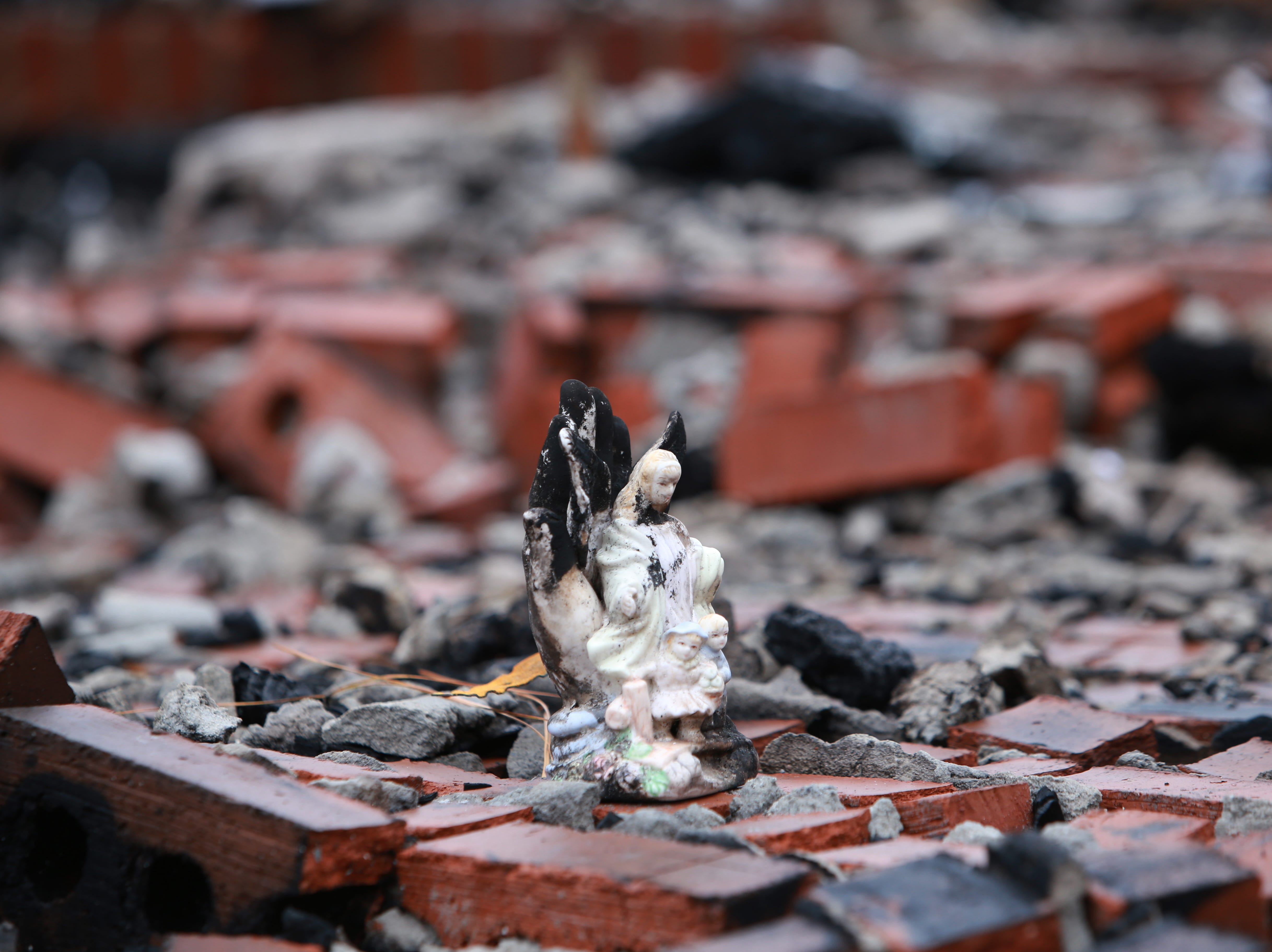 An angel figurine was one of the possessions left in the rubble of a house fire that destroyed the Haas home in Kiln, Mississippi, on Nov. 25, 2018.