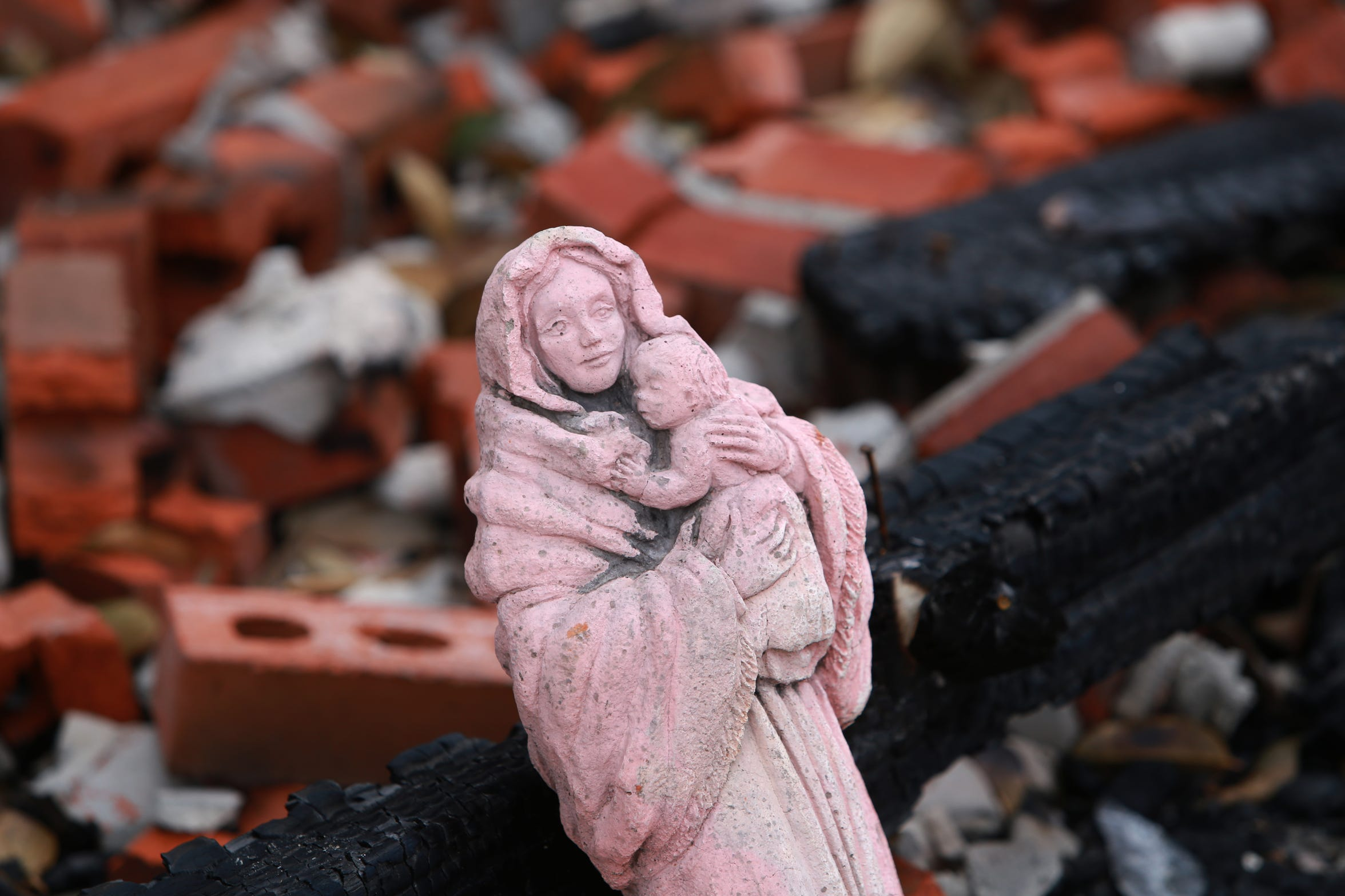 """Mother and Child,"" a statue of the Blessed Mother and Jesus, is one of the only possessions left in a house fire that destroyed the Haas family home in Kiln, Miss., on Nov. 26, 2018."