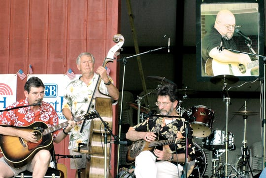 FILE: Jeff  Long on the guitar, right, Sarge McCann on the upright bass, center, and Bruce Nemerov, left, playing guitar, are part of group of friends that get together to play once a year and they played May 14, 2005, in memory of their dear friend radio personality Rusty Mac during the first Pickin' for Rusty Mac music event held at the Casey Jones Amipitheater.  A portrait of Rusty Mac hangs at back of the stage.