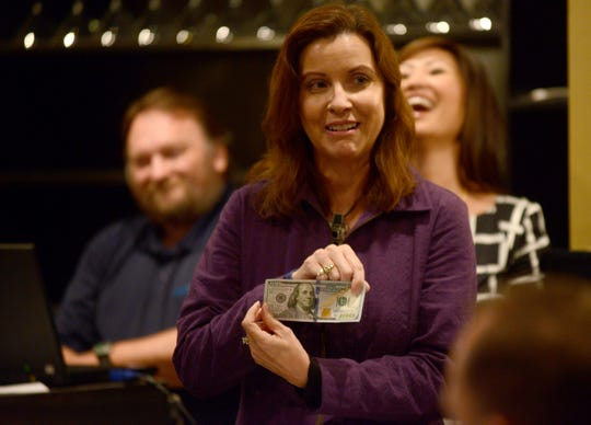In this file photo from 2014, Rita McCaslin shows a $100 bill, which is what it takes to support a teen this Christmas for the Rusty Mac Adopt-a-Teen Project.