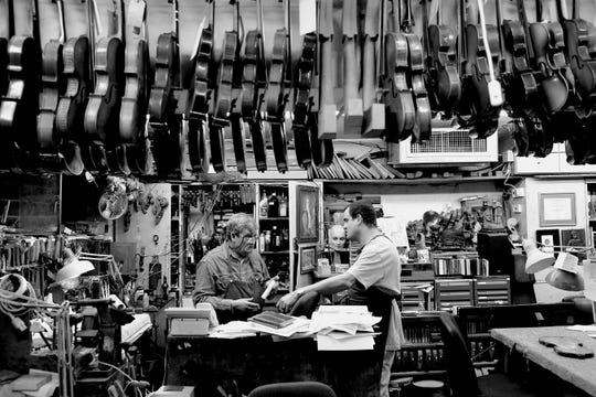 Israeli violin makers and restorers Amnon Weinstein and his son Avshalom Weinstein stand among the violins in their workshop.