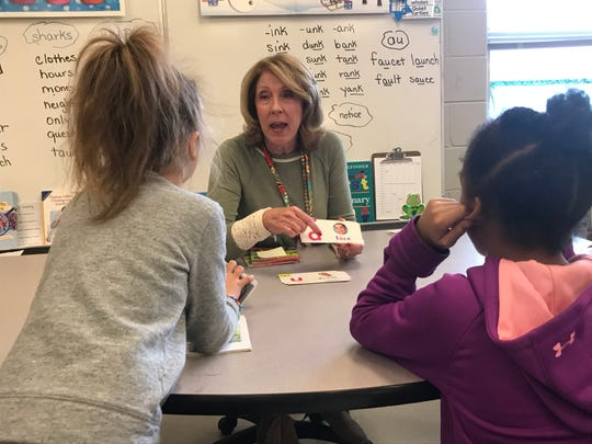 Substitute teacher Lisa Hildebrand runs through words with Pond Gap Elementary School students during an indoor recess.
