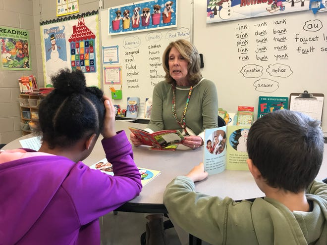 Substitute teacher Lisa Hildebrand assists Pond Gap Elementary School second-graders with reading. Hildebrand has subbed for Knox County Schools for 15 years.