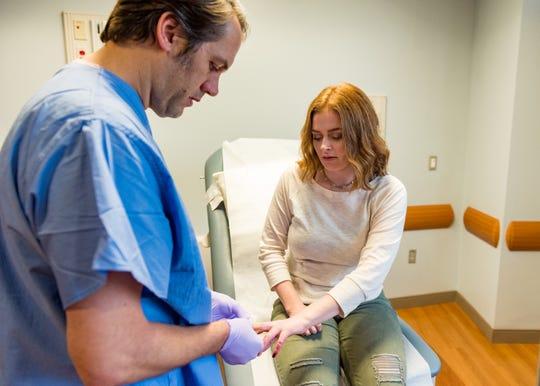 Burn Nurse, Ryan Butcher treats Abbie's healing fingers during one of her regular check-ups at the burn clinic