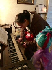 """Marie and Avery Guidry get some help playing """"Joy to the World"""" on an historic piano inside Rosedown Plantation in St. Francisville Sunday, Dec. 9, 2018."""