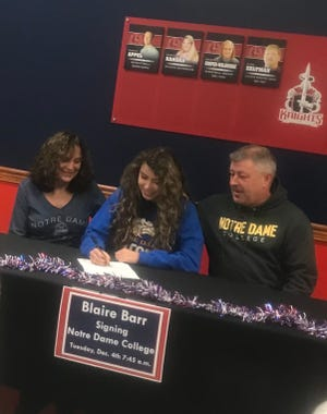 With her parents beside her, Fairfield Christian Academy's Blaire Barr signs her letter of intent to play volleyball at Notre Dame College. Barr earned first All-Ohio honors this season and is the two-time-Mid-State League-Cardinal Division Player of the Year.