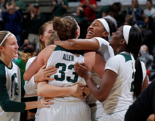 Michigan State's Claire Hendrickson, from left, Jenna Allen (33), Sidney Cooks and Mardrekia Cook celebrate following an 88-82 win over Oregon in an NCAA college basketball game, Sunday, Dec. 9, 2018, in East Lansing, Mich. Michigan State won 88-82. (AP Photo/Al Goldis)