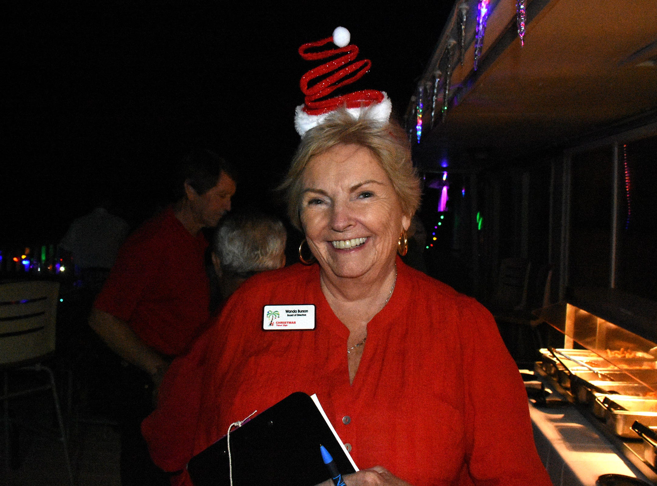 Head judge Wanda Day relaxed atop the Snook Inn after the parade passed. The Christmas Island Style boat parade lit up Marco waterways Saturday evening.