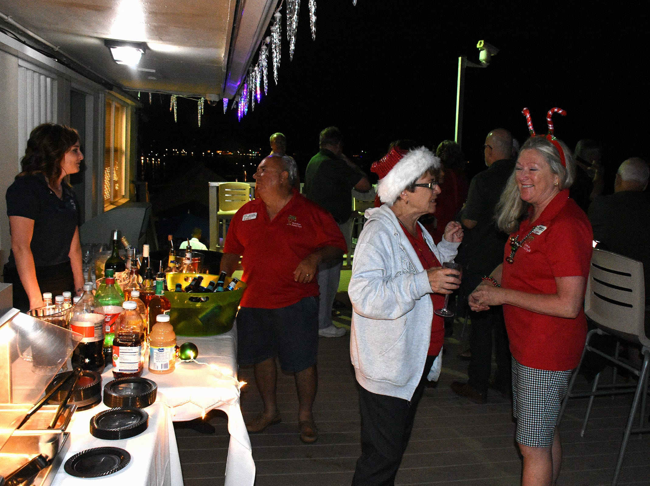 Bette McGilvray, right, talked with Barbara Dasti at the judges' stand atop the Snook Inn during the Christmas Island Style boat parade lit on Marco Island.