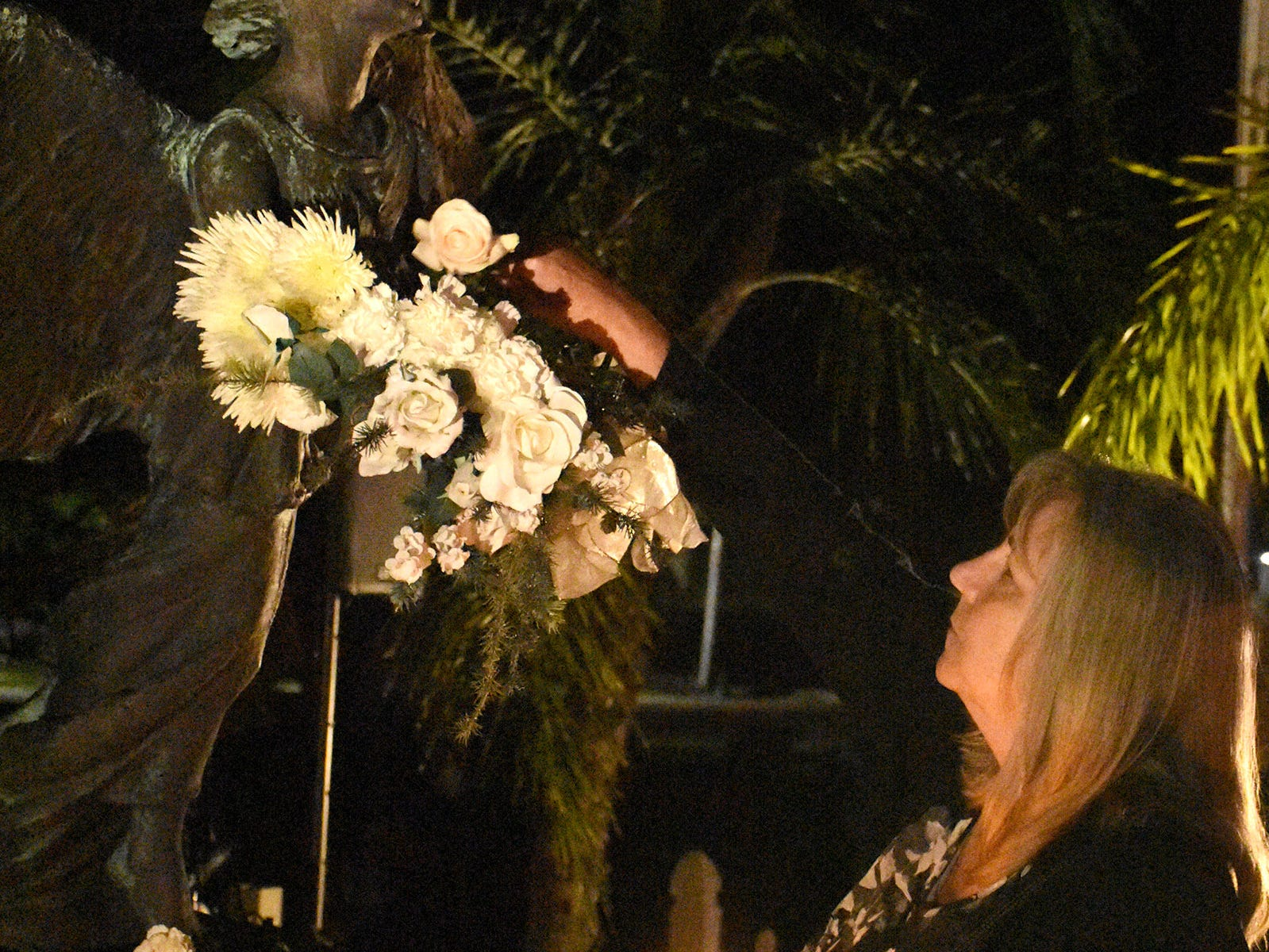 Mourners lay flowers on the angel at the end of the Marco Island Christmas Box Angel Memorial Service on Thursday evening.