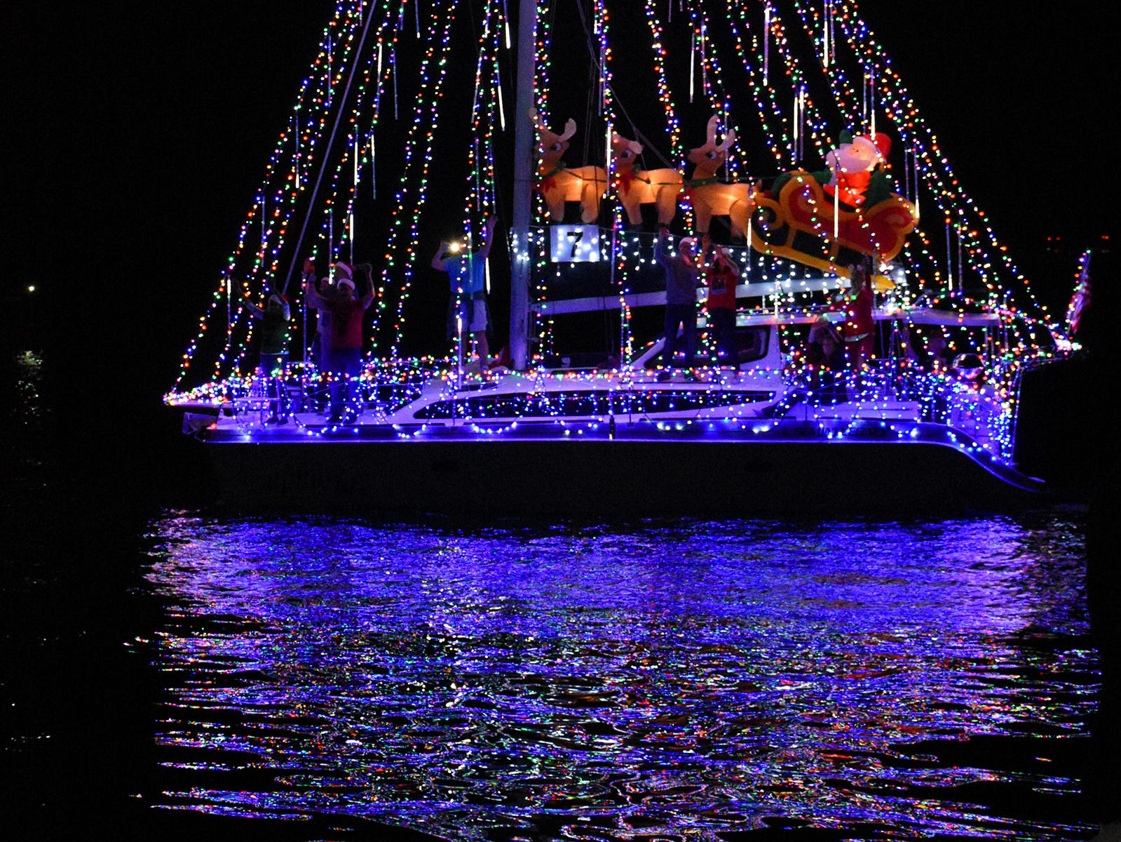 """Best in Parade winner, Capt. Mike Rushalk's """"Euphoria"""" cruises past the Snook Inn. The Christmas Island Style boat parade lit up Marco waterways Saturday evening."""