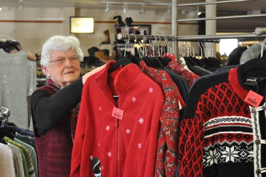 Doris Barelmann, a volunteer, organizes holiday sweaters at the Family Sharing of Ozaukee County resale store. Proceeds from the retail store help fund the food pantry next door.