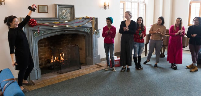 Philosophy club members look on as club president Danielle Ayn Burdick (left) dedicates the improved fireplace in Caroline Hall at Mount Mary University. The club led the effort to convert the fireplace to natural gas and allow more frequent use.
