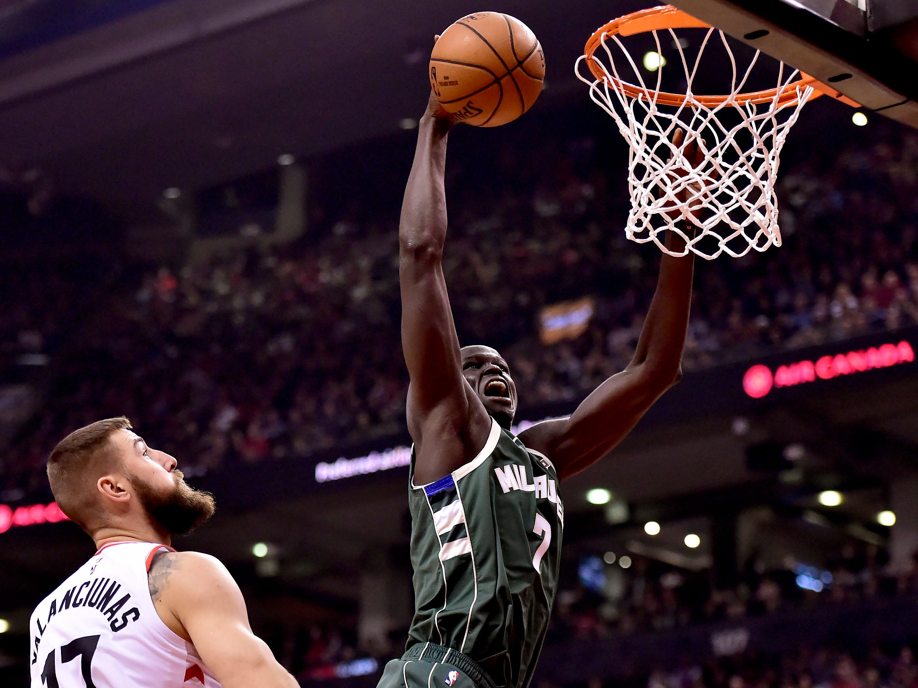 Toronto Raptors center Jonas Valanciunas (17) watches as Milwaukee Bucks forward Thon Maker (7) dunks during first-half NBA basketball game action in Toronto, Sunday, Dec. 9, 2018. (Frank Gunn/The Canadian Press via AP)