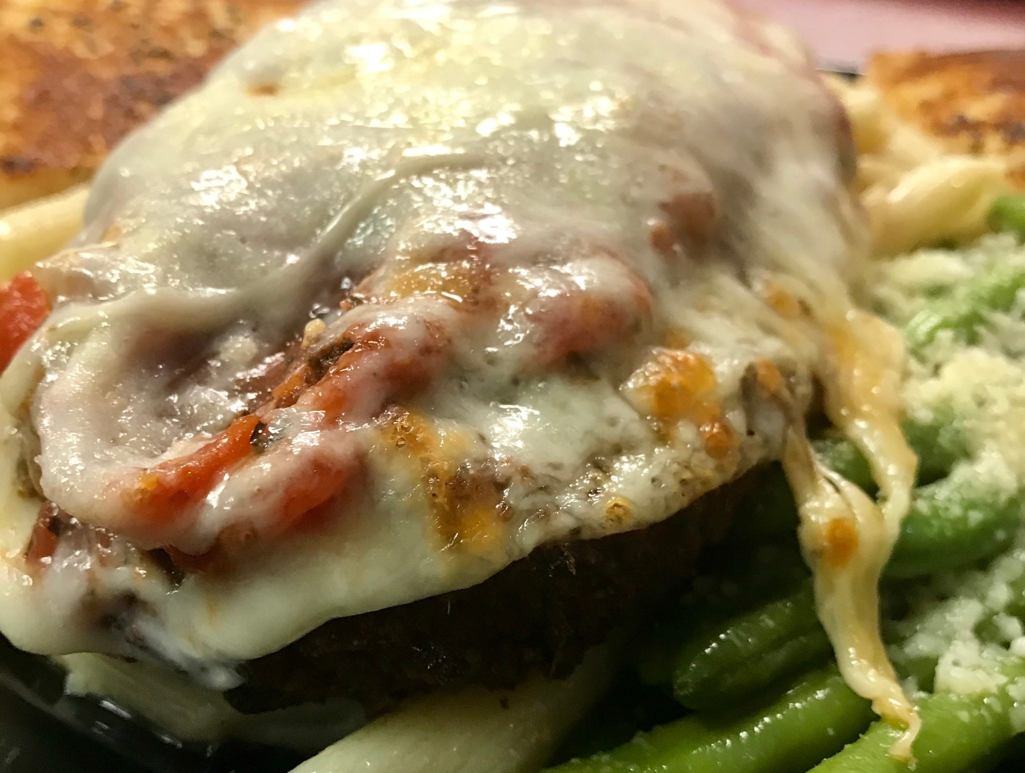The chicken parmesan is served atop a bed of garlic butter ziti pasta with green beans and garlic bread.