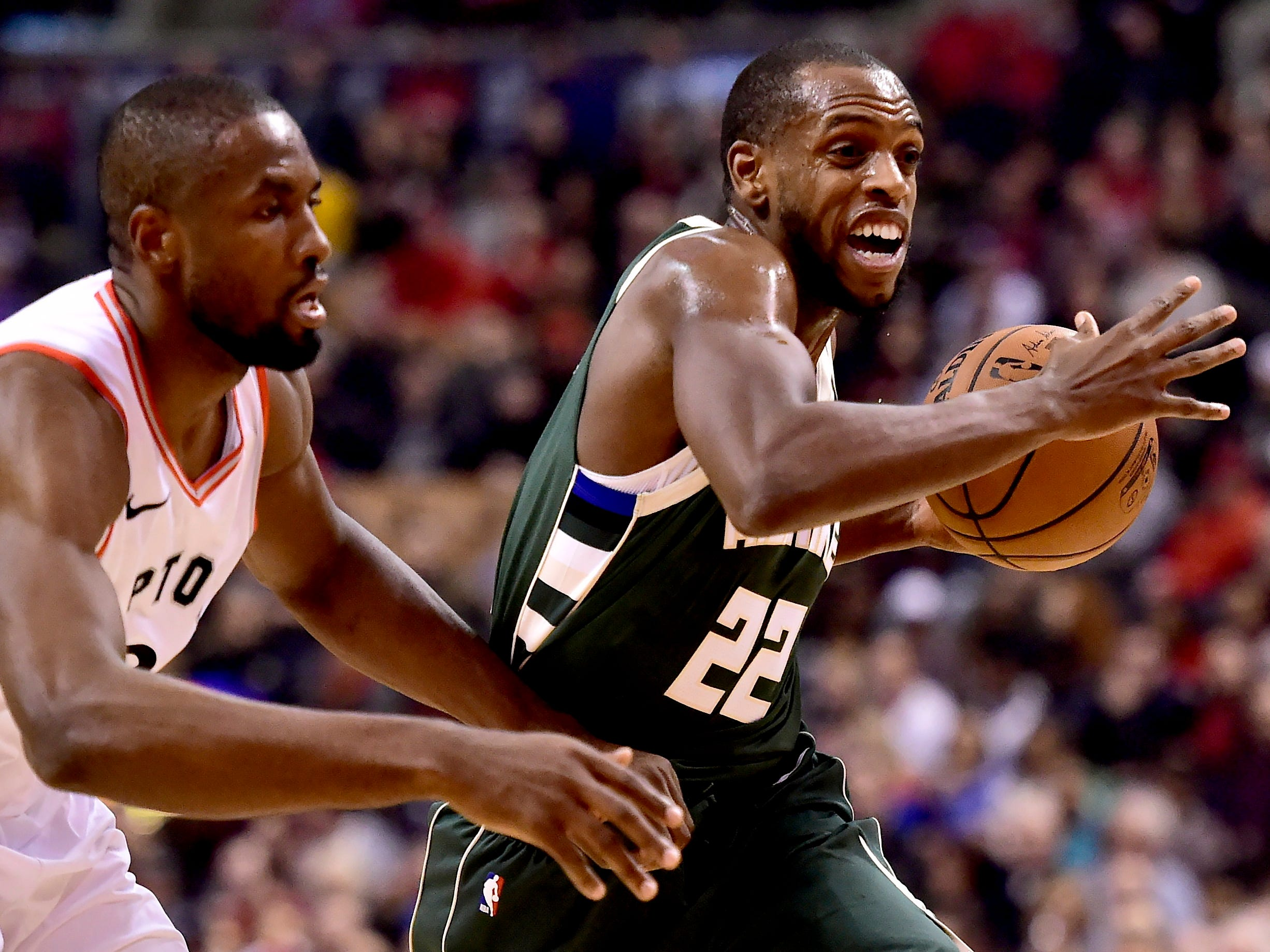 Toronto Raptors forward Serge Ibaka, left, watches Milwaukee Bucks forward Khris Middleton (22) as he drives to the net during first-half NBA basketball game action in Toronto, Sunday, Dec. 9, 2018. (Frank Gunn/The Canadian Press via AP)