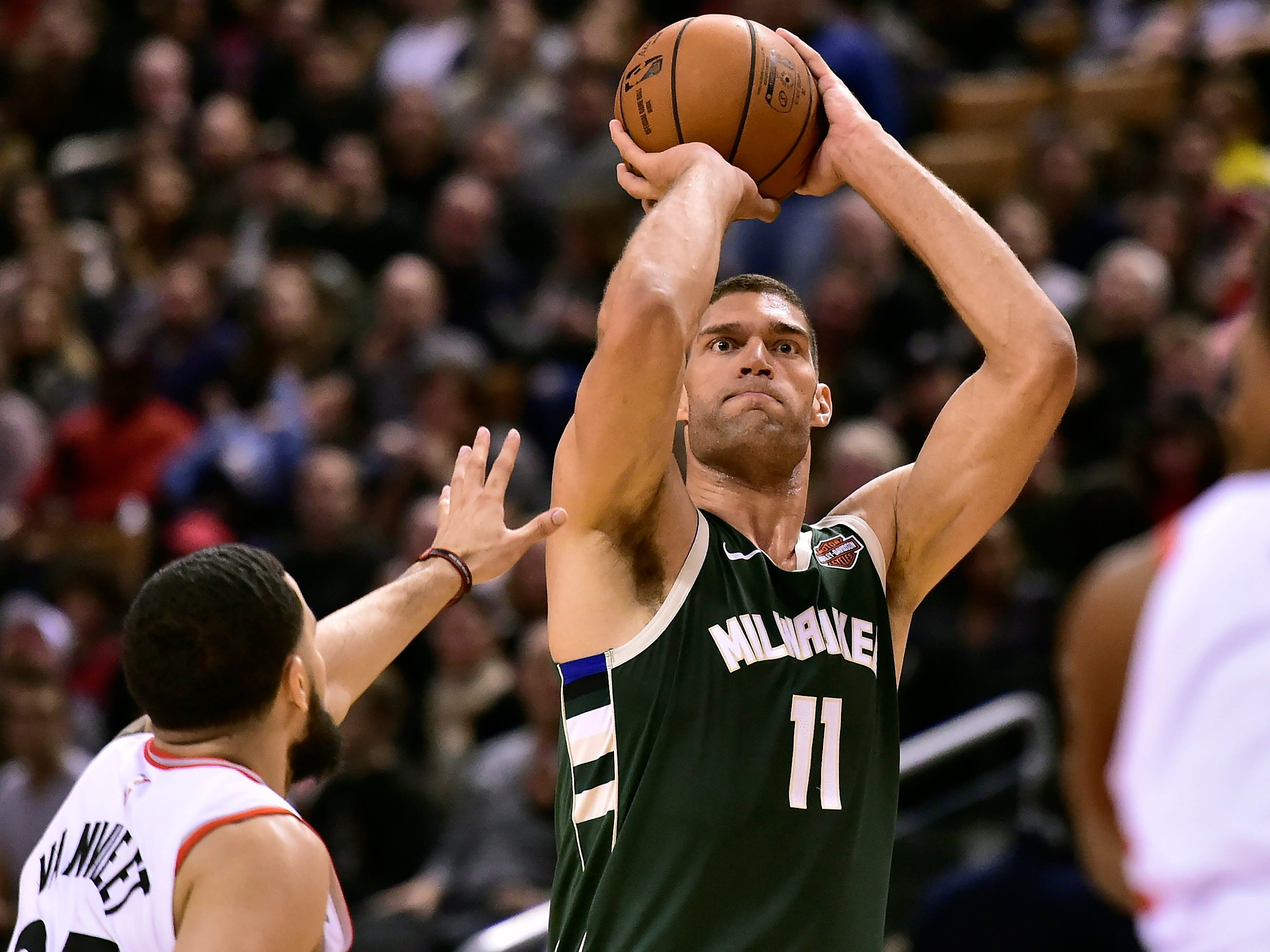 Milwaukee Bucks center Brook Lopez (11) lines up a three point shot as Toronto Raptors guard Fred VanVleet (23) attempts to defend during first half NBA basketball action in Toronto on Sunday, Dec. 9, 2018. (Frank Gunn/The Canadian Press via AP)