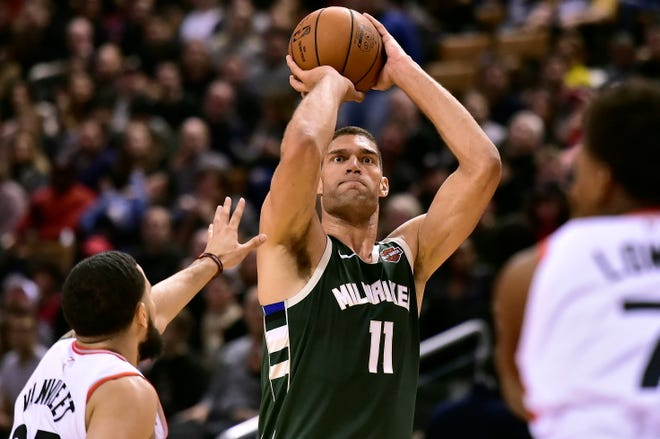 Bucks center Brook Lopez lines up a three-point shot Sunday. He sank five of them and finished with 19 points.