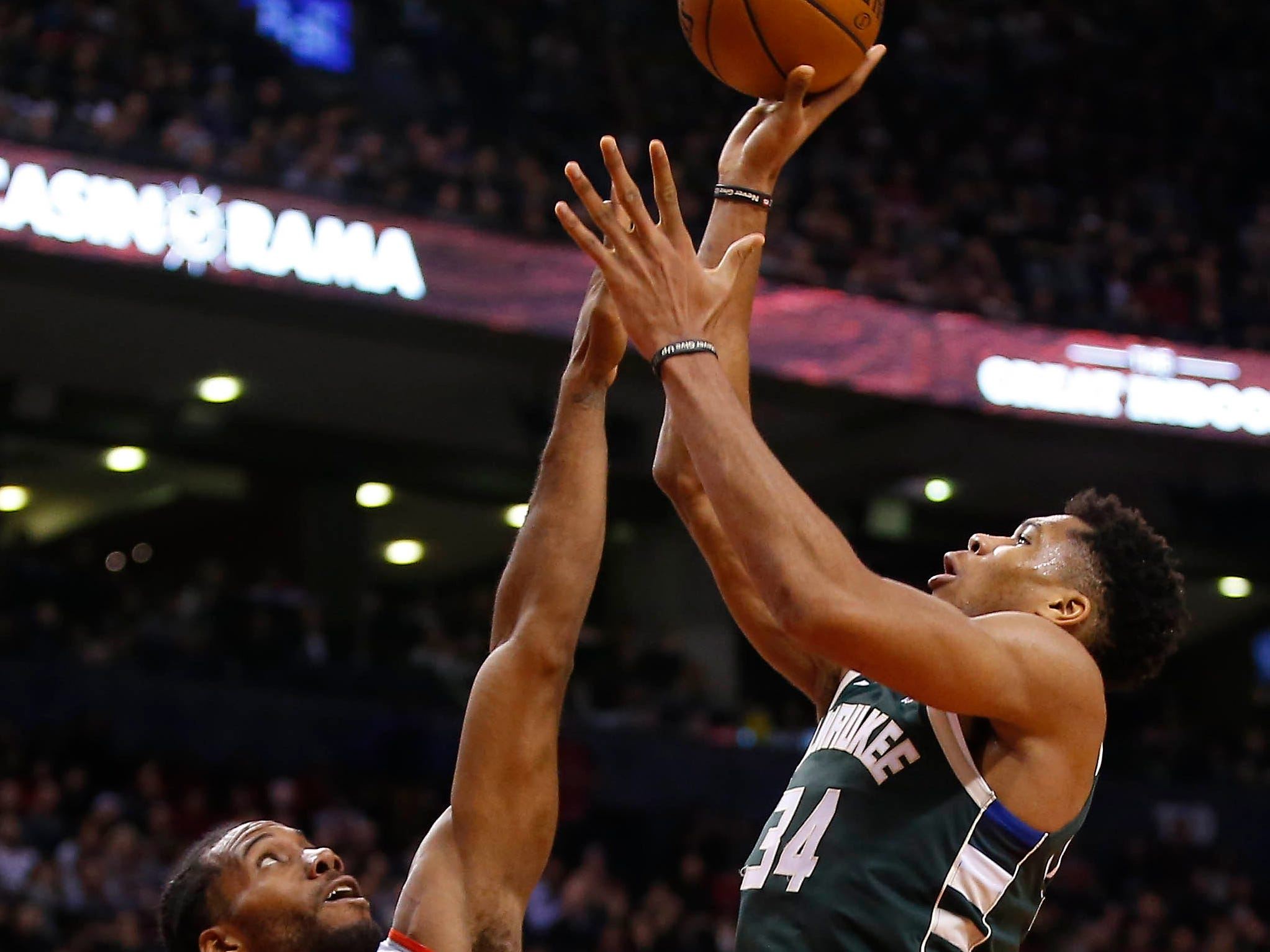 Dec 9, 2018; Toronto, Ontario, CAN; Milwaukee Bucks forward Giannis Antetokounmpo (34) goes up to make a basket against Toronto Raptors forward Kawhi Leonard (2) at Scotiabank Arena. Milwaukee defeated Toronto. Mandatory Credit: John E. Sokolowski-USA TODAY Sports