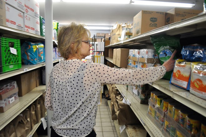 Lucy Weller, the food pantry manager at Family Sharing of Ozaukee County, organizes shelves in the food pantry.