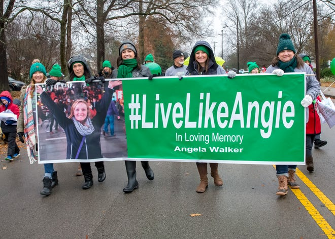 """The Murfreesboro Christmas parade was dedicated to the memory of Angie Walker, the former """"parade boss"""" who died in the Christiana tornado Nov. 6. Holding a sign in memory of their friend are, from left, Beth Spivey, Julianna Craddock, Tracy Tucker, Katie Criswell and Tamara Heilig-Ludlam."""