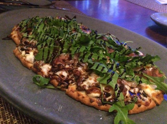 Prosciutto-pear flatbread topped with arugula and balsamic glaze at Decker & Dyer.