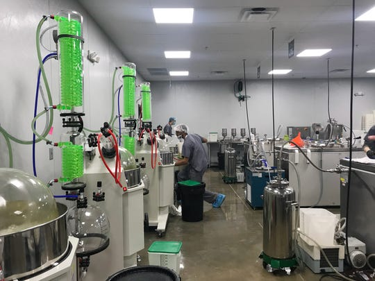 Trulieve employees work in the CO2 extraction room, where the process of removing any trace amounts of toxins in the finished cannabis product begins, at the Quincy, Fla., facility in December 2018.