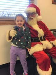 Finley Barnhill, age 5 and daughter of firefighter Tom Barnhill, stayed warm inside and talked with Santa while awaiting more toy drop offs at Fire Station 1 in Pataskala on Saturday. Another drop off is planned for Dec. 15 at Station 1 from 9 a.m. to noon.