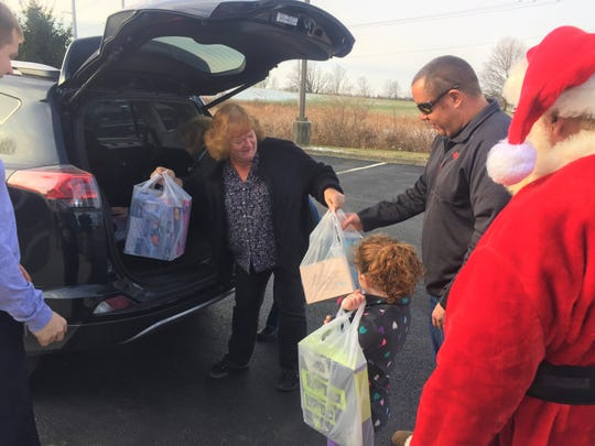Colleen Rice and Jani Garza drop off toys Dec. 8 to the West Licking Firefighters, including Firefighter Tom Barnhill and daughter Finley, as Santa Claus looks on.