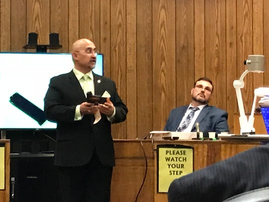 Assistant Prosecutor Jorge Morales in court holding a .45 pistol, one of two weapons the state believes was used in the Rodriguez slaying.