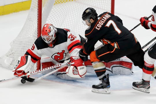 New Jersey Devils goaltender Cory Schneider, left, blocks a shot by Anaheim Ducks left wing Andrew Cogliano during the second period of an NHL hockey game in Anaheim, Calif., Sunday, Dec. 9, 2018.