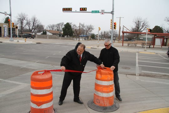 (From left)-John Waters, director of the Carlsbad Department of Development and Rick Rudometkin, Eddy County manager, move orange barrels in place during a ribbon cutting ceremony dedicating the reopening of Standpipe Road.